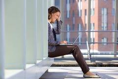 坐外面使用膝上型计算机的愉快的女商人 免版税库存图片