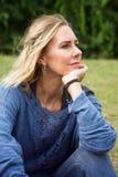 坐外面在公园的白肤金发的妇女 库存照片