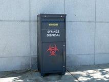 坐外面在圣Fra的注射器处置/生物危害品罐 库存照片