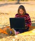 坐女孩的膝上型计算机户外 库存照片
