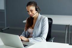 坐她的计算机的Infront电话中心操作员 免版税库存图片