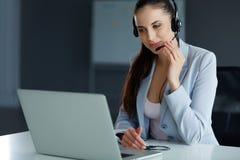 坐她的计算机的Infront电话中心操作员 免版税库存照片