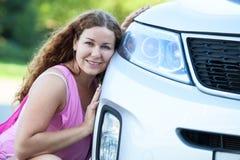 坐她的面颊的俏丽的女孩反对对汽车防撞器  免版税库存照片