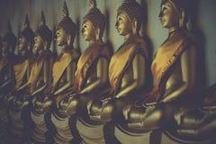 坐姿势的金黄菩萨雕象行在泰国 免版税库存照片