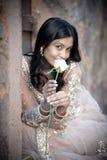 坐对石墙的年轻美丽的印地安妇女户外 免版税库存照片