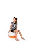 坐对等待的球海滩逗人喜爱的女孩作&# 免版税图库摄影