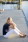 坐少年水的码头女孩 免版税库存照片