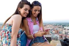 坐屋顶和听到音乐的美丽的女孩在su 免版税图库摄影