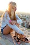 坐屋顶和听到音乐的美丽的女孩 免版税库存照片