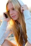 坐屋顶和听到音乐的美丽的女孩 图库摄影