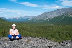 坐山上面和看照相机的妇女 免版税库存图片