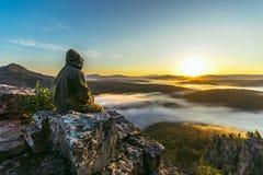 坐山峰顶和遇见美好的日出的一个旅游人 免版税图库摄影