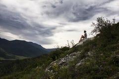 坐山顶面和冥想天空的美丽的妇女覆盖 库存照片