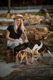 坐岩石和宠爱好狗的草帽的美丽的白肤金发的妇女 同一种颜色 泰国的海滩 早晨结构 图库摄影