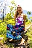 坐岩石和摆在为照片,女孩的美丽的少女穿着花卉最大的裙子,在的自然微笑的背景 库存照片