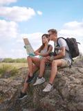 坐岩石和看地图的美好的年轻夫妇 免版税库存照片