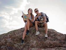 坐岩石和看地图的美好的年轻夫妇 免版税库存图片