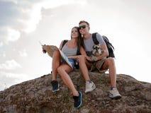 坐岩石和看地图的美好的年轻夫妇 免版税图库摄影