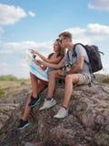 坐岩石和看地图的美好的年轻夫妇 库存图片