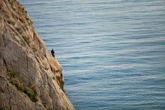 坐岩石和钓鱼晴天的渔夫 免版税图库摄影