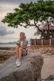 坐岩石由海和听到与您的片剂的音乐的美丽的白肤金发的妇女 有纹身花刺的手 样式 图库摄影