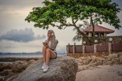 坐岩石由海和听到与您的片剂的音乐的美丽的白肤金发的妇女 有纹身花刺的手 样式 库存图片