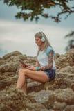 坐岩石由海和听到与您的片剂的音乐的美丽的白肤金发的妇女 有纹身花刺的手 样式 库存照片