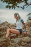 坐岩石由海和听到与您的片剂的音乐的美丽的白肤金发的妇女 有纹身花刺的手 样式 免版税库存图片