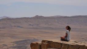 坐峭壁` s边缘和看在沙漠附近的太阳镜的少妇 库存图片