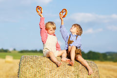 坐干草堆和吃椒盐脆饼的两个小孩 免版税库存照片
