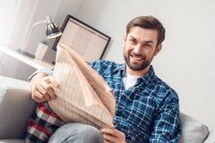 坐年轻人的休闲在家拿着报纸快乐 免版税库存图片
