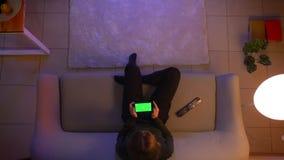 坐年轻俏丽的女性特写镜头顶面射击播放在电话的录影有绿色屏幕的,当看着电视和时 股票视频