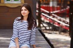 坐年轻美丽的长发的女孩户外 城市步行, yo 库存图片