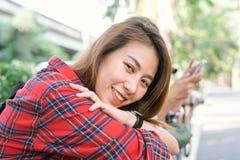 坐并且微笑享受她的城市生活方式的年轻亚裔妇女沿街道在周末等待的一个早晨室外 免版税库存照片
