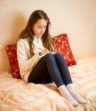 坐床和写诗的十几岁的女孩在日志 免版税库存照片