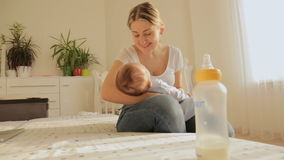 坐床和晃动她的3个月的美丽的年轻母亲婴孩在喂养他以后 股票视频