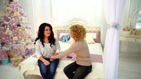 坐床在有欢乐圣诞树的明亮的卧室在冬日两个美妙的女朋友的乐趣和笑话  影视素材