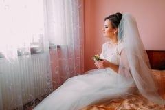 坐床在结婚的生活梦想的窗口附近和举行逗人喜爱的小的婚礼钮扣眼上插的花的美丽的新娘 免版税库存图片