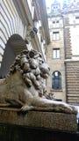坐开罗Kasr El尼罗在样式背景前面的石头狮子古老雕塑,石强的雕象 库存图片