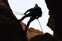 坐式下降法从岩石的登山人 免版税库存图片