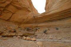 坐式下降法从干燥瀑布的登山人 免版税库存图片