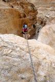坐式下降法从干燥瀑布的登山人 库存图片