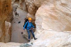 坐式下降法从干燥瀑布的登山人 免版税图库摄影