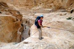 坐式下降法从干燥瀑布的登山人 库存照片