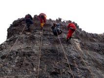 坐式下降法使用唯一绳索技术的四个登山人 库存照片