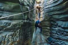 坐式下降法的瀑布 潜水衣攀登的人在狭窄的河峡谷的瀑布 库存图片
