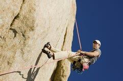 坐式下降法从峭壁的人 库存图片
