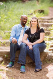 坐微笑的人种间的夫妇外面 免版税库存照片