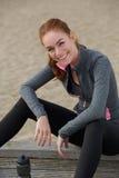 坐微笑的体育的妇女户外 免版税库存照片