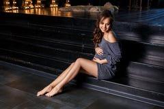 坐怀孕的女孩摆在健康母性的概念 库存照片